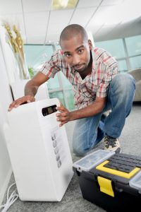 Crouching by an air conditioning unit